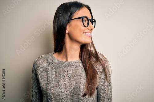 Fotografiet Young beautiful brunette woman wearing casual sweater and glasses over white background looking away to side with smile on face, natural expression