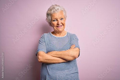 Senior beautiful grey-haired woman wearing casual t-shirt over isolated pink background happy face smiling with crossed arms looking at the camera Canvas Print