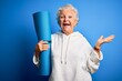 Senior beautiful sporty woman holding mat for yoga standing over isolated blue background very happy and excited, winner expression celebrating victory screaming with big smile and raised hands