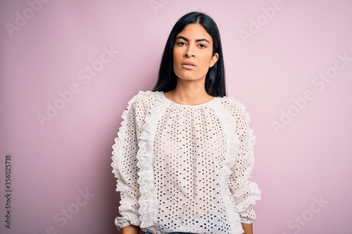 Photo Young beautiful hispanic fashion woman wearing elegant shirt over pink background with serious expression on face