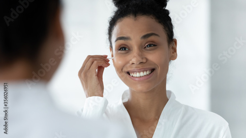 Fototapeta Mirror reflection head shot close up smiling African American young woman cleaning ears, beautiful girl wearing white bathrobe using cotton bud after shower, morning routine, personal hygiene obraz
