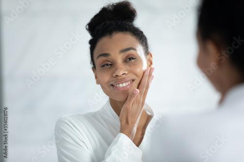 Fotografia Head shot smiling African American woman touching cheek, enjoying perfect smooth