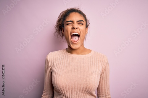 Tela Young beautiful african american girl wearing casual sweater standing over pink background angry and mad screaming frustrated and furious, shouting with anger