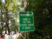 Green Warning Trail At The Dam Floods When It Rains Sign