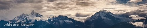 Obraz Panoramic shot of rocky mountains under a cloudy sky - perfect for natural concepts - fototapety do salonu