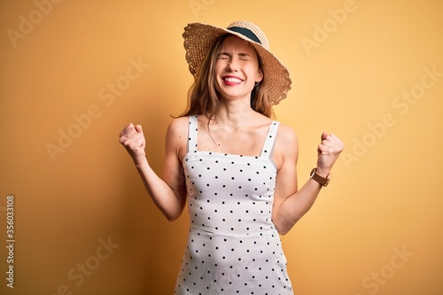 Cuadros en Lienzo Young beautiful blonde woman on vacation wearing summer hat over yellow background very happy and excited doing winner gesture with arms raised, smiling and screaming for success