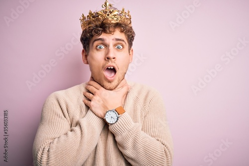 Young blond man with curly hair wearing golden crown of king over pink background shouting and suffocate because painful strangle Wallpaper Mural