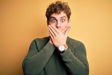 Young Blond Handsome Man With Curly Hair Wearing Green Sweater Over Yellow Background Shocked Covering Mouth With Hands For Mistake. Secret Concept.