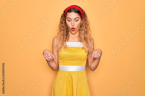 Photo Beautiful blonde pin-up woman with blue eyes wearing diadem standing over yellow