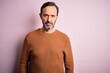 Middle age hoary man wearing casual brown sweater standing over isolated pink background with serious expression on face. Simple and natural looking at the camera.