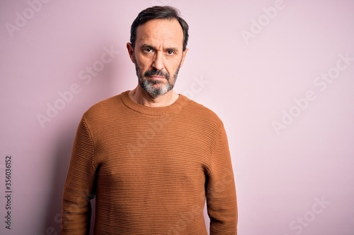 Slika na platnu Middle age hoary man wearing casual brown sweater standing over isolated pink background with serious expression on face