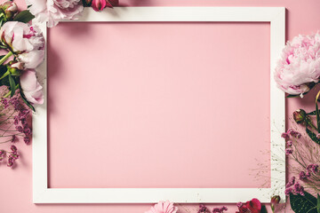 Assorted pink flower and white frame border on pink background, flat lay