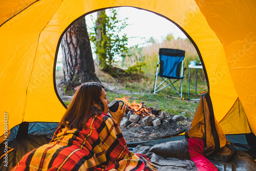 woman laying in yellow tent looking at bonfire