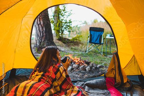 Fototapeta woman laying in yellow tent looking at bonfire