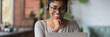 Leinwandbild Motiv African girl wear headphones looks at pc screen watch movie, online webinar, enjoy virtual study with tutor, teacher interact with trainee via video call, horizontal banner for website header design