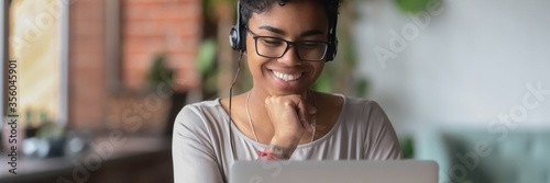 African girl wear headphones looks at pc screen watch movie, online webinar, enjoy virtual study with tutor, teacher interact with trainee via video call, horizontal banner for website header design - 356045901