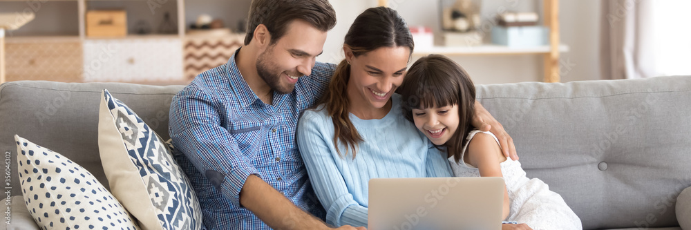 Fototapeta Couple and little daughter sit on sofa using pc watching cartoons on-line, surfing internet, buying via e-commerce web sites, spend weekend at home. Horizontal photo banner for website header design