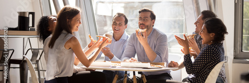 Photo Multiethnic staff gathered together in office kitchen enjoy lunch eat pizza telling funny life stories laughing