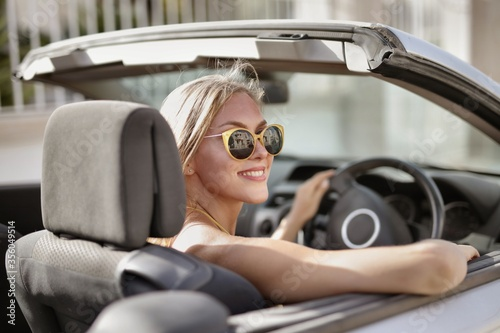 Blonde woman with sunglasses driving a car Fototapet