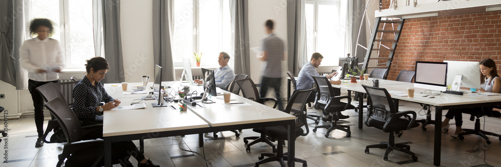 Fototapeta Group of multi ethnic corporate employees working in co-working open space walking in motion, sit at shared desks. Busy workday, office rush concept. Horizontal photo banner for website header design