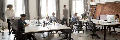 Fototapeta Group of multi ethnic corporate employees working in co-working open space walking in motion, sit at shared desks. Busy workday, office rush concept. Horizontal photo banner for website header design obraz