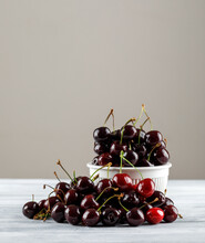 Black Cherries In A Bowl On Grungy And Grey Gradient Background. Side View.
