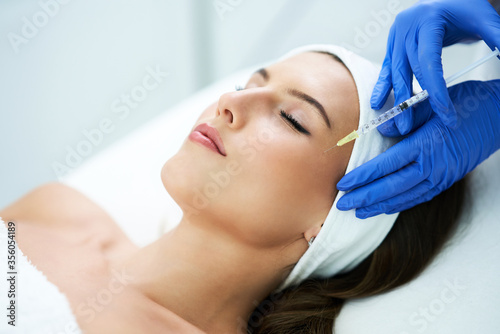 Fotografie, Obraz Beautiful young woman getting acid face treatment at beauty salon