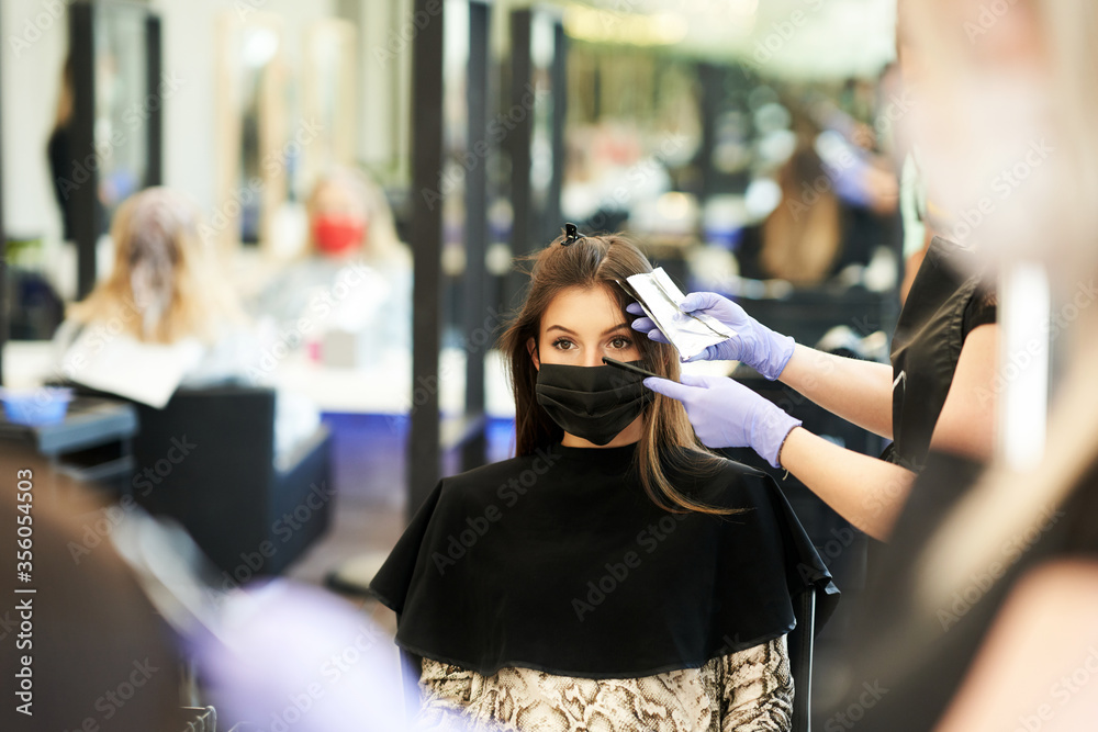 Fototapeta Adult woman at hairdresser wearing protective mask due to coronavirus pandemic