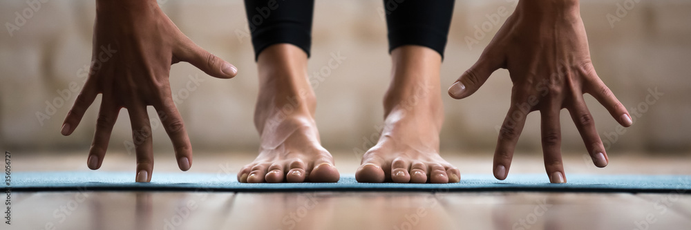 Fototapeta Horizontal photo banner for website header design sportive woman performing forward bend practising yoga uttanasana asana pose. Barefoot legs in pants on yogic mat palms close up view wellness concept