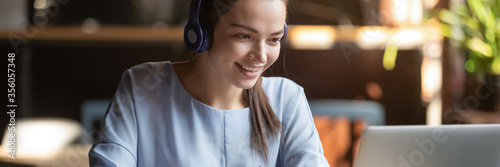 Woman wear headphones look at pc enjoy study online with tutor, listen audio lecture watch webinar prepare for exams, e-learn, self education concept Fototapeta