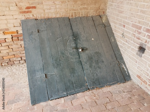 red bricks and locked black wood door to cellar