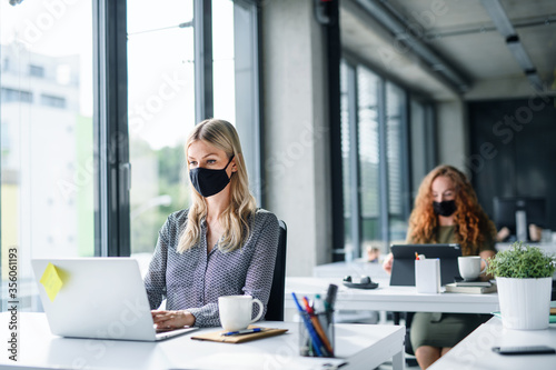 Cuadros en Lienzo Young people with face masks back at work or school in office after lockdown