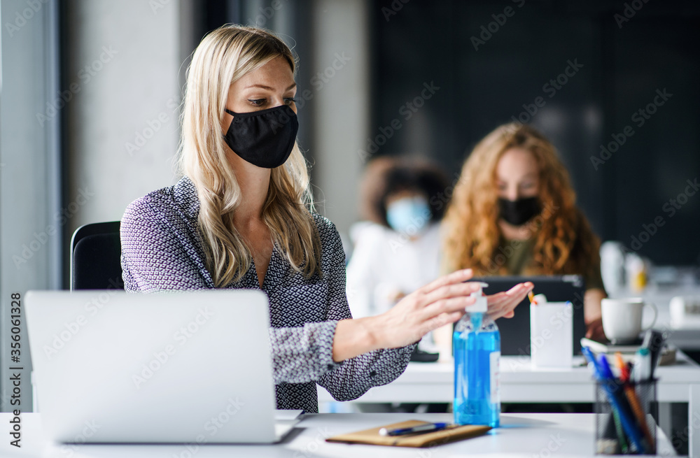 Fototapeta Young woman with face mask back at work in office after lockdown, disinfecting hands.