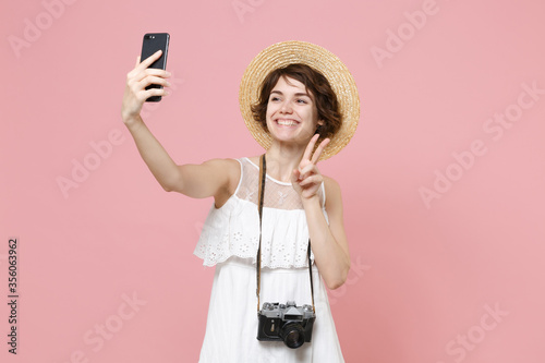 Fotografía Smiling tourist girl in dress hat photo camera isolated on pink background