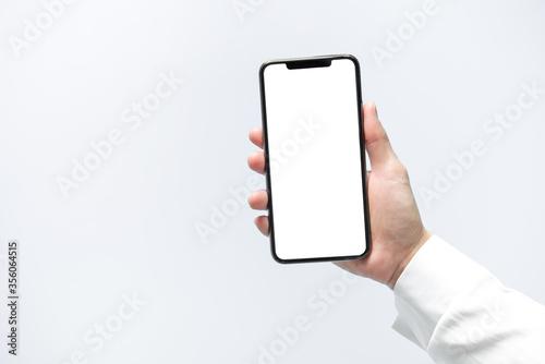 Fototapeta Smartphone mockup. Businesswoman hand holding black phone white screen. Isolated on white background. Mobile phone frameless design concept. obraz