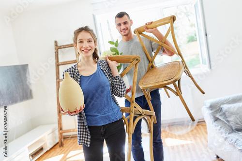 Leinwand Poster Junges Paar mit Stühlen und Pflanzen beim Einzug