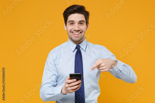 Fotomural Smiling young business man in classic blue shirt tie posing isolated on yellow background studio