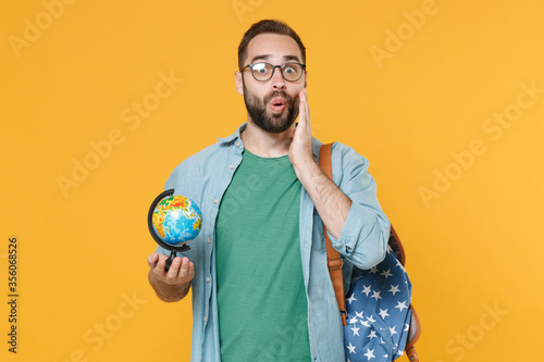 Photo Shocked young man student in casual clothes glasses with backpack isolated on yellow wall background studio