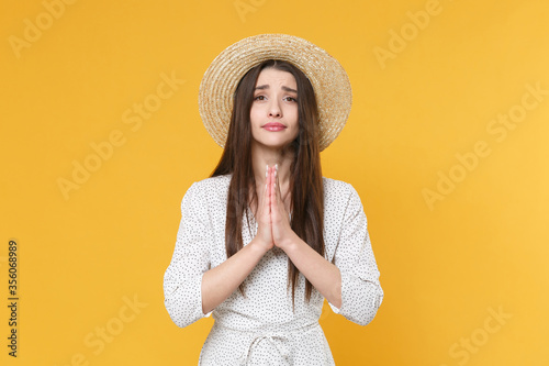 Obraz na plátne Pleading young brunette woman girl in white dress hat posing isolated on yellow background studio portrait