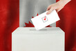 Leinwandbild Motiv Canadian Vote concept. Voter hand holding ballot paper for election vote on polling station