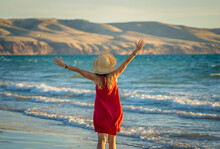 Woman In Red With Arms Outstretched By The Sea At Sunrise Enjoying Freedom And Outdoors Life