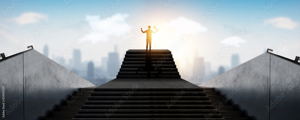 Fototapeta successful businessman, success business, achievement people holding award,trophy standing on top of stair over city