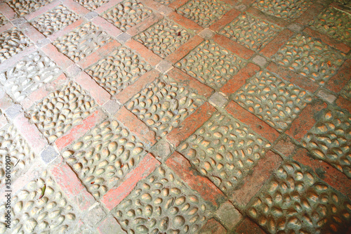 A brick laid floor in a diamond pattern inlaid with beach pebbles to create this Victorian floor of diamonds with quartz cobbles фототапет