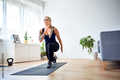 Fotografie, Tablou Happy athletic woman doing home workout practicing lunges exercise