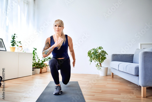 Valokuvatapetti Fit woman doing lunges exercise during home workout