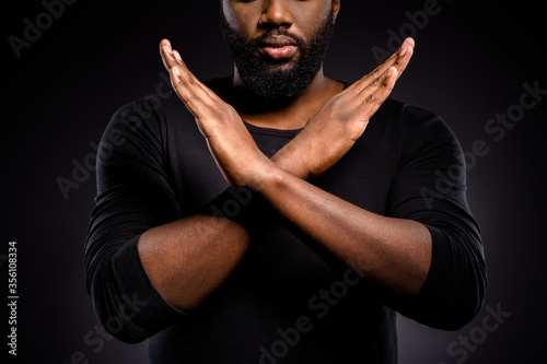 Leinwand Poster Cropped photo of serious afro american guy revolution activist cross hands x ask