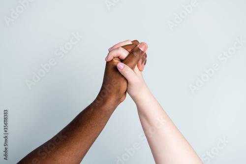 Closeup photo of two hands arms different race multinational couple best friends Fototapet