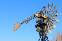 Rusty Windpump Old West Against Blue Sky With Moon