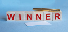 WINNER Word On Cube Blocks With Pen And Business Card On Blue Table. Winner Concept