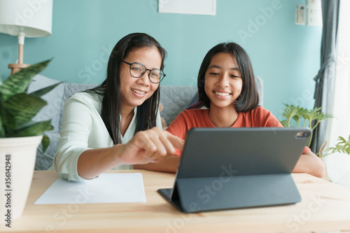 Asian family with daughter do homework by using tablet with mother help Fototapet